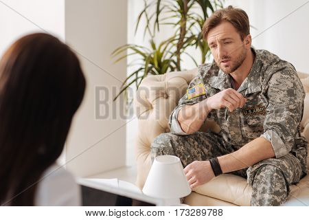 Psychological trauma. Distressed cheerless military man sitting on the sofa and speaking with his therapist while having a psychological session