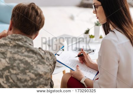 Psychologists notes. Close up of preliminary diagnosis written by a professional therapist during the physiological session with a soldier from US army