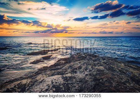 Dramatic sunset on the sea shore. Tropical colourful sunset and view of dark night sea with protruding stones in Nang Thong Beach, Khao Lak, Thailand.