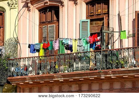 Clothes hanging from colonial style antique balconies.