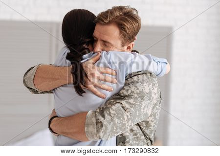 Long awaited meeting. Handsome delighted nice soldier standing and hugging his wife while coming home from the mission