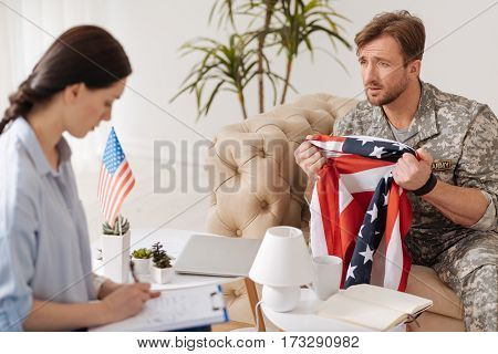 Patriotic feelings. Sad unhappy military man having the American flag in his hands and looking at the psychologist while having a psychological session