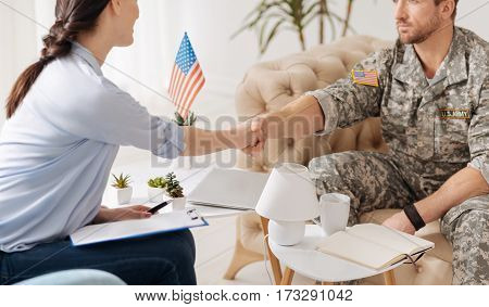 Thank you for help. Nice handsome military man sitting in the sofa and giving a handshake while being grateful for help