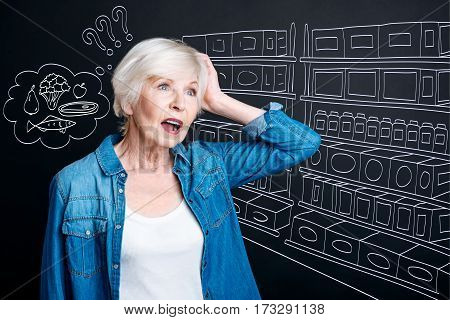Buying food. Pleasant emotional anxious woman standing in the supermarket and holding her head while trying to remember what she needs to buy