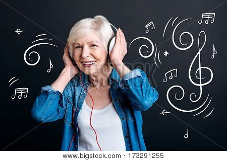Pleasant entertainment. Delighted happy elderly woman wearing headphones and listening to music while entertaining himself