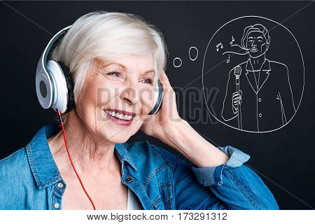 Favourite music. Cheerful nice aged woman listening to her favourite singer and smiling while listening to music