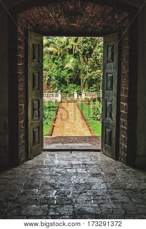 Open doors to the tropical garden the paved road to the door of the old Indian Villa.Vintage stone floor and walls.
