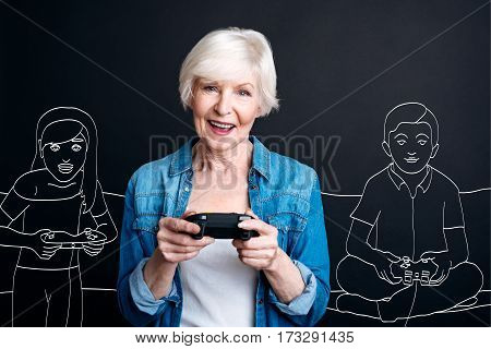Interaction with grandchildren. Happy positive elderly woman holding a game console and playing video games while spending time with her grandchildren