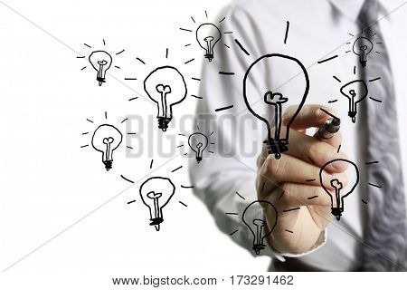 businessman drawing light bulb on whiteboard