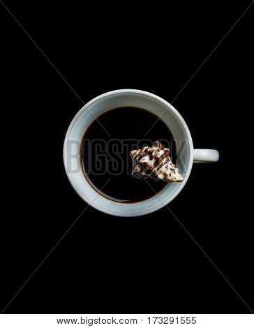 Splash of coffee and milk in white cup isolated on black background