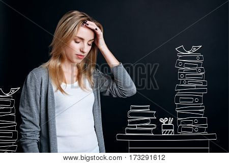 Too much studying. Hard working tired unhappy student holding her head and being surrounded by books while having a headache