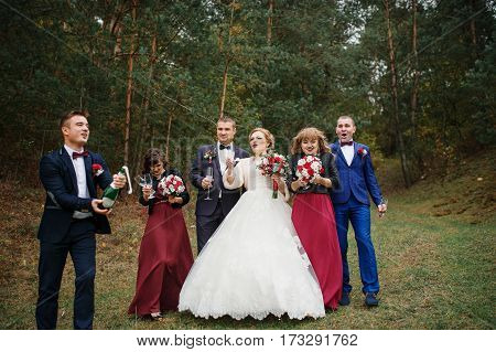 Wedding Couple With Friends Bridesmaids And Groomsman Drinking Champagne At Wood.