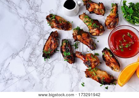 Chicken wings in orange sauce baked on a marble background