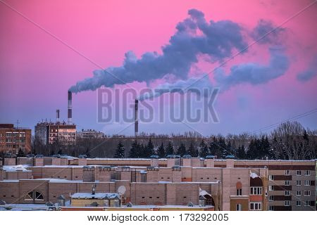 Purple winter sky and smoking plant pipes over the industrial city