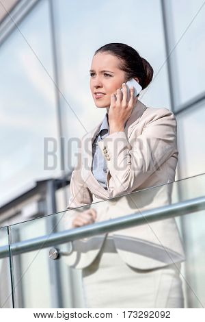 Young businesswoman using smart phone at office railing