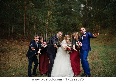 Wedding Couple With Friends Bridesmaids And Groomsman At Wood.