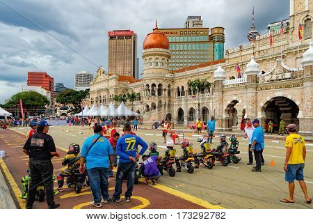 Kuala Lumpur, Malaysia - February 7, 2016: Kids riding at one mini-bike junior competition on training near Sultan Abdul Samad Building. The team at the start beginning of the competition.
