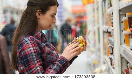 woman buys honey in supermarket or store