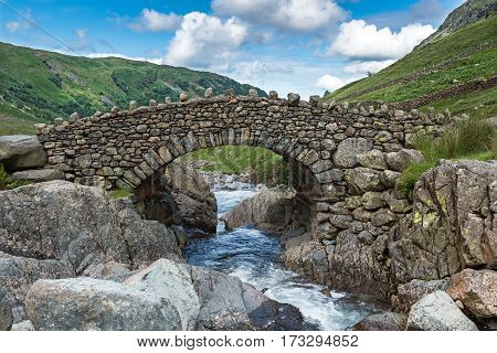 Stockley Bridge spans Grains Gill in the Lake District National Park, Cumbria. The bridge forms part of the footpath to Green Gable mountain and is a popular walking route to Green Gable mountain.