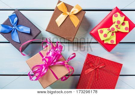 Colorful gift boxes on nice blue wooden background.