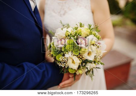 Close Up Wedding Bouquet At Hands Newlyweds.