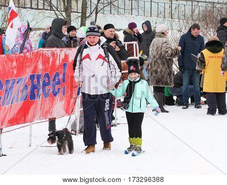Kirishi, Russia - 11 February, The man with the dog and the girl on skis, 11 February, 2017. Mass ski race Russian Ski Track.