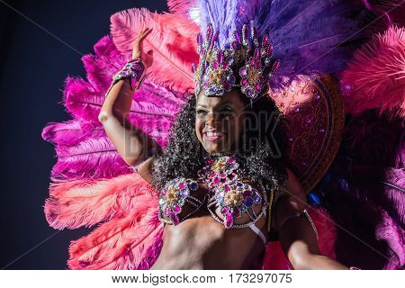 MOSCOW, RUSSIA- JANUARY 2017: Brazilian carnival show. Beautiful girl bright colorful carnival costume dark background. Smiling Afro-Americans woman samba dancer pink carnival costume black background