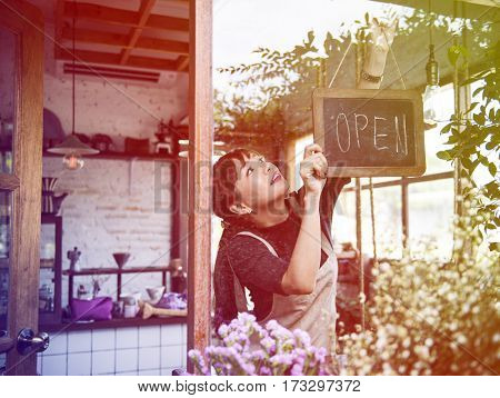 Young woman holding banner open the flower shop