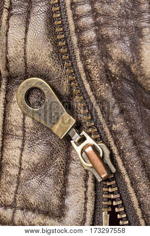 Close-up zipper on old brown leather jacket. Focus on zipper.