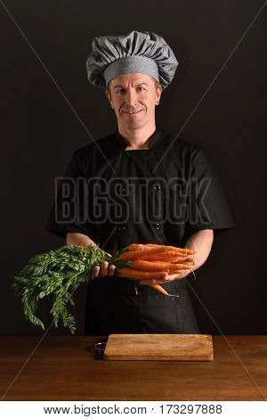 chef chopping a carrot on black background