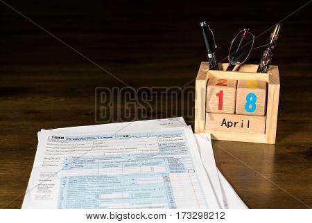 Wooden letters in calendar with Form 1040 income tax for 2016 showing tax day for filing is April 18 2017