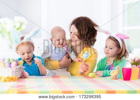 Mother and children painting colorful eggs. Mom toddler preschooler and baby with bunny ears paint and decorate Easter egg. Parent and kids play indoors in spring. Family celebrating Easter at home.