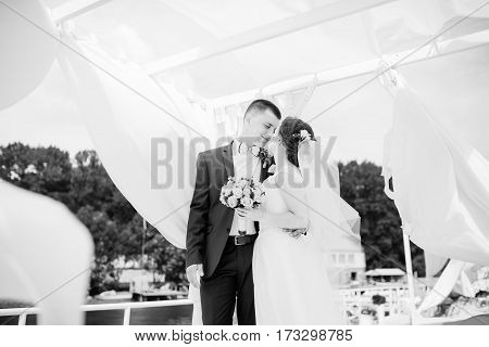 Charming Wedding Couple Hugging On Pier Of The Dock Under Bungalow. Black And White Photo.