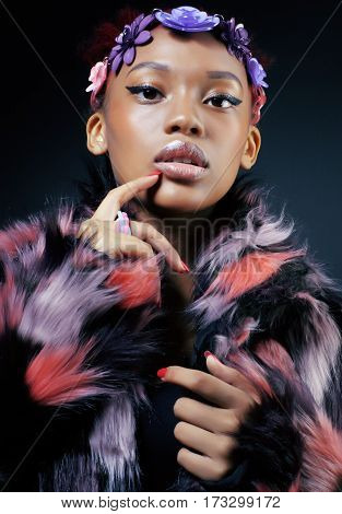 young pretty african american woman in spotted fur coat and flowers jewelry on head smiling sweet etnic make up bright close up