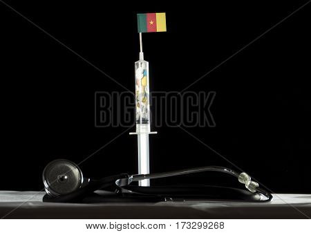 Stethoscope And Syringe Filled With Drugs Injecting The Cameroonian Flag On A Black Background