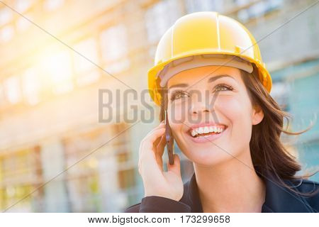 Young Professional Female Contractor Wearing Hard Hat at Construction Site Using Cell Phone.