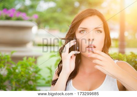 Shocked Young Adult Female Talking on Cell Phone Outdoors on Bench.