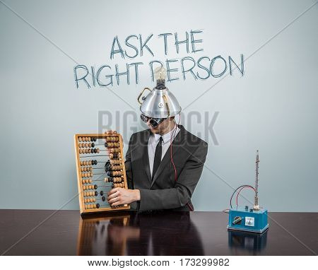Ask the right person text on blackboard with businessman and abacus