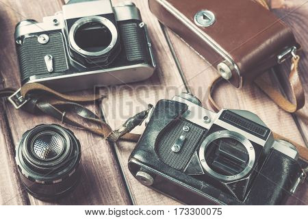 Old film camera with lens and case on wooden background. Vintage toned and selective focus.