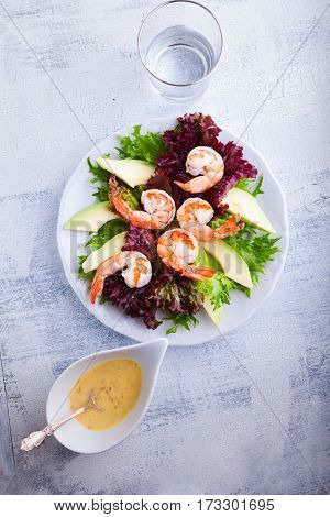 Avocado shrimp salad with mustard sauce on a white plate