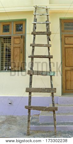 old wooden ladder against a Bangkok temple wall