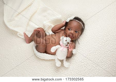 Portrait of a one month old newborn baby girl. She is holding a stuffed bear and lying on a soft cream colored faux sheepskin blanket.