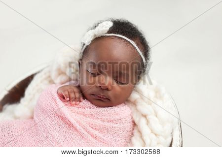 Portrait of a one month old sleeping newborn baby girl. She is swaddled in pink and sleeping in a tiny bucket.