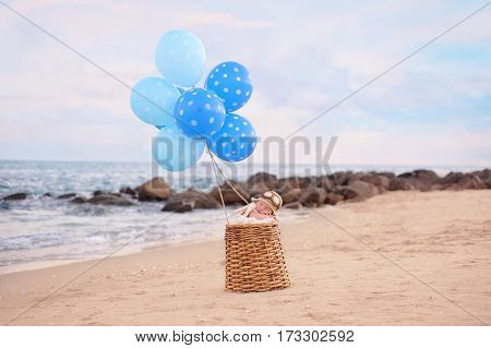 Two week old newborn baby boy sleeping in a wicker basket with blue balloons. He is wearing an aviator hat. Photographed on a beach with a rock jetty.