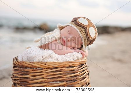 Two week old newborn baby boy sleeping in a wicker basket wearing an aviator hat. Photographed on a beach with a rock jetty.