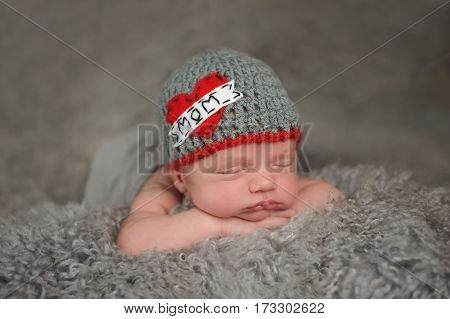 Two week old sleeping baby boy wearing a crocheted