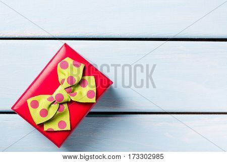 Red gift box with nice butterfly on blue wooden background. Free space for text.