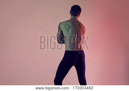 Sexy sporty sport fit man. Muscular naked torso from back on a red background.