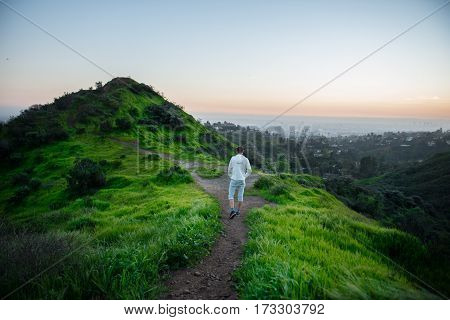 Tourist man walking on green mountain trail at sunset time