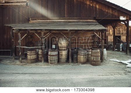 Old vintage Barrels near retro style wooden barn. Wild west concept photo.
